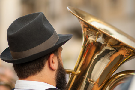 man plays his tuba during an outdoor party