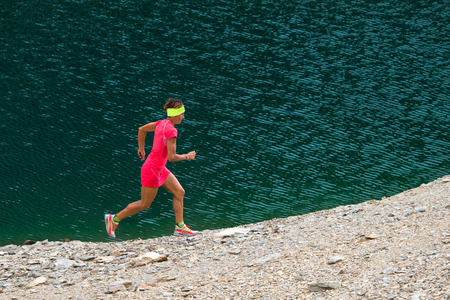 stride: Girl with athletic body with full pink runs near a lake