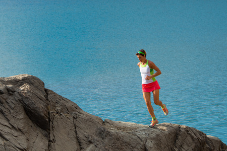 large rocks: Woman trains running on large rocks on the lake Stock Photo