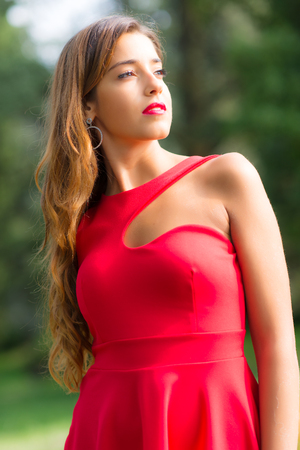 girl in red dress: Beautiful girl with red dress looks into the sun Stock Photo