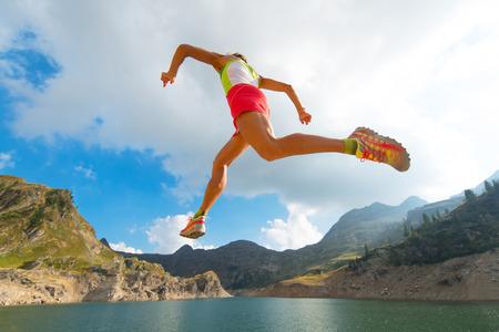 stride: Skipping girl as he runs near a mountain lake wide stride Stock Photo