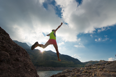 Girl training run while jumping near an alpine lake in the mountains at sunset