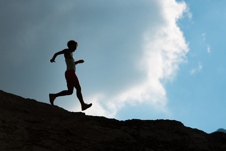 stride: Silhouette of woman running on rocks downhill in the mountains