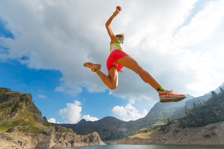 stride: Skipping girl as he runs near a mountain lake skirt racing Stock Photo