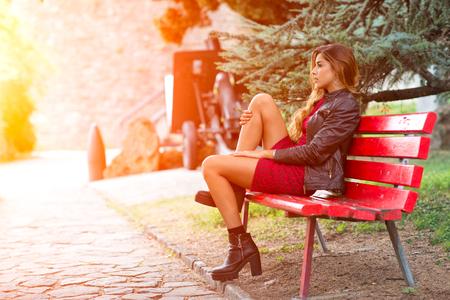 miniskirt: Girl in miniskirt sitting on a red bench