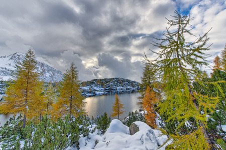 silently: Seasons meet, fall and winter in the alpine lake with colorful plants