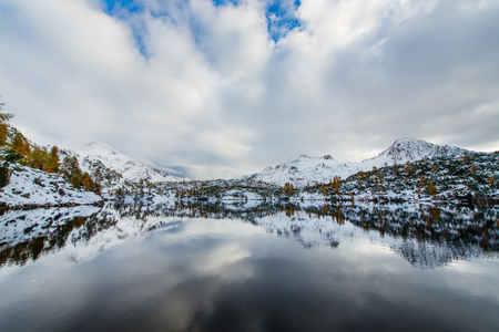 reflected: Mountains reflected in alpine lake with first snow Stock Photo