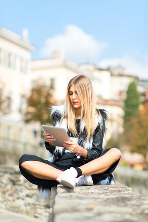 persona leyendo: Chica con la tableta en una pared en la ciudad