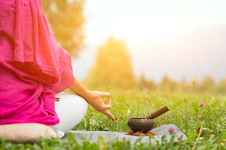 Tibetan bell beside yoga position in a meadow the sun Banque d'images