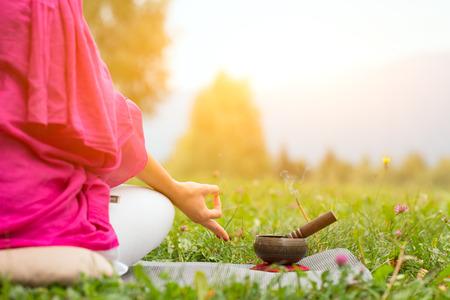 Tibetaanse bel naast de yoga-positie in een weiland de zon