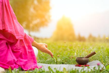 yoga position: Tibetan bell beside yoga position in a meadow