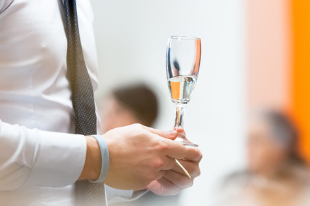 glas sekt: Glas Sekt in der Hand eines Mannes in der Gleichheit bei einem Aperitif
