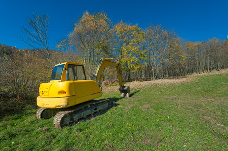 dig: Excavator in a field ready to dig