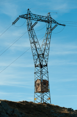 small house: A curious electricity pylon with inside a small house Stock Photo