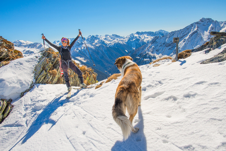 touring: Girl ski touring in the mountains with dog is happy