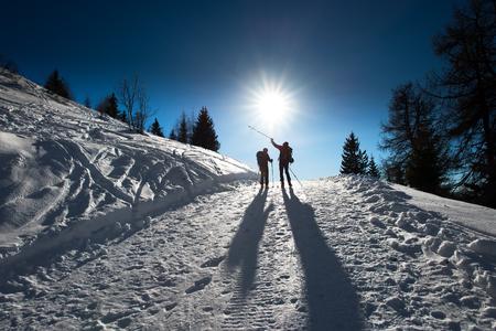 indicate: Alpine skiers uphill indicate mountain