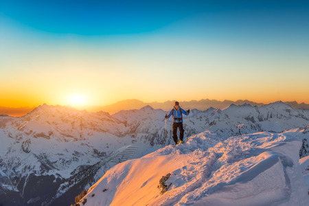 atop: Mountaineer almost atop the summit in winter at sunset Stock Photo