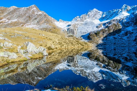 Alpine landscape with autumn snow mountains that are reflected in the lake
