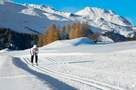 Woman in a cross-country skiing on the tracks