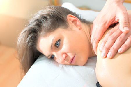 Masseur doing massage on woman body in the spa center. Stock Photo