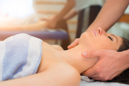 Therapist massaging the neck of woman In the spa center