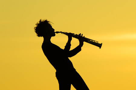 listening to music: Playing saxophone silhouette on yellow background