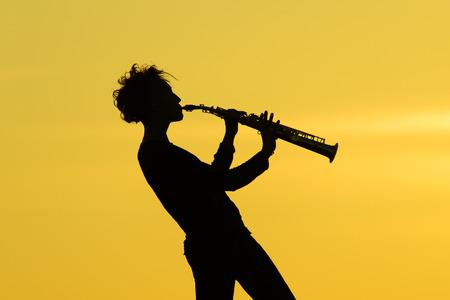 soprano saxophone: Que juegan la silueta saxofón sobre fondo amarillo Foto de archivo
