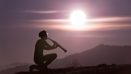 sax: Sax player in purple sky at sunset Stock Photo