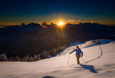 Ascending to the top. Ski mountaineering Cross country skiing alone uphill into silence at sunset