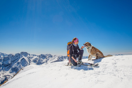 touring: Girl ski touring with his dog at the top of the mountain Stock Photo