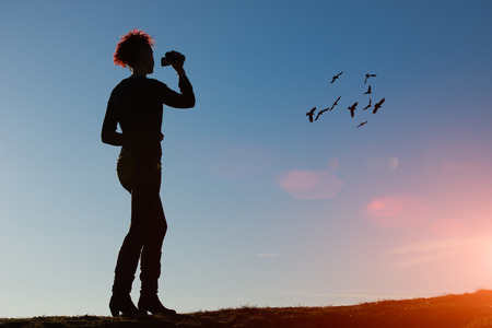 filming: Woman with video camera filming birds in the sky Stock Photo