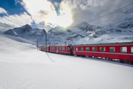 Swiss mountain train Bernina Express crossed through the high mountain snow