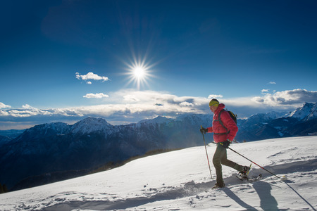 The man in snowshoes and with trekking poles In the high mountains in the sun