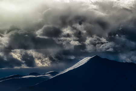 scenical: Clouds with spectacular colors in a winter mountain landscape Stock Photo