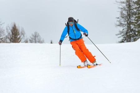 downhill: One man practicing skiing downhill mountain climbing Stock Photo