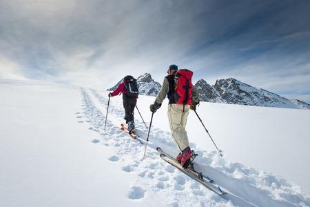 Dvě starší alpské lyžaři vylézt na lyžích a tuleních kůží