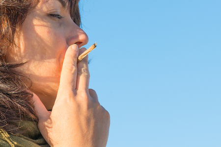 Woman smoking a cigarette joint