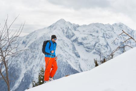 mountaineering: Man alone with ski mountaineering climb towards the summit Stock Photo
