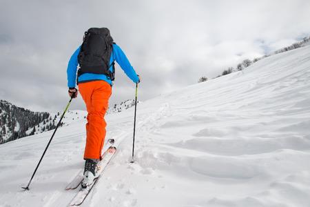 Man alleen met ski bergbeklimmen klim naar de top