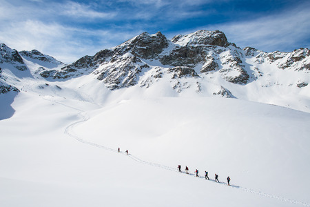 Group of climbers roped to the summit in the winter Stock Photo