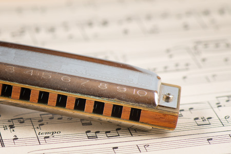 aerophone: Harmonica resting on sheet music in detail