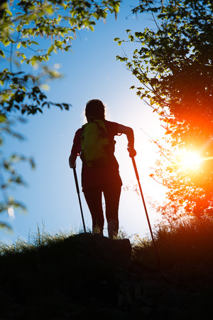 nordic nature: Nordic walking towards the sun in the nature of a single girl Stock Photo