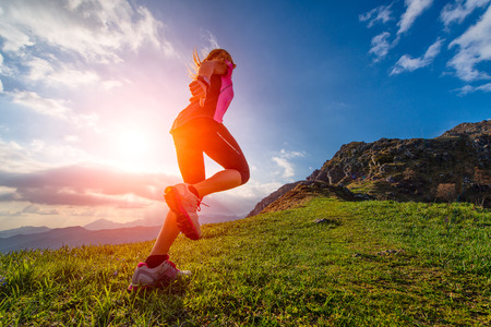 Action athletic of a girl running mountain into the sunset