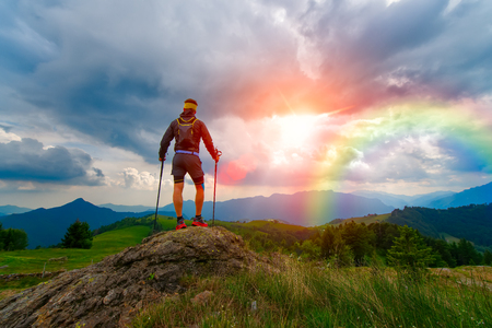 panoramas: Man in the mountains at sunset looks rainbow in a divine sky Stock Photo