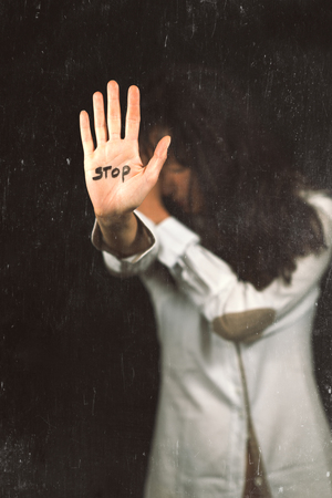 Stop violence against women. Hand saying stop. Image that seems ruined
