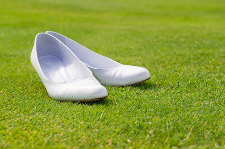 particular: particular of white wedding shoes on grass