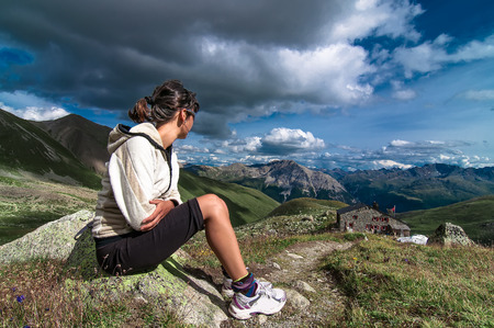 observed: Woman sitting in the mountains observed an alpine hut and the view in the summer