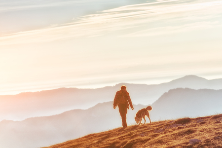 Man walking with his dog in the mountains around sunset