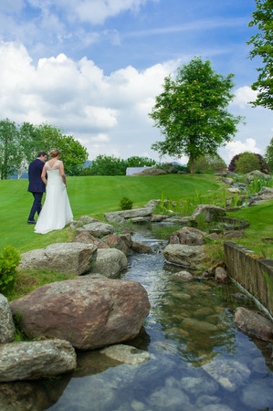 togheter: groom and bride walking on the grasss near the river Stock Photo