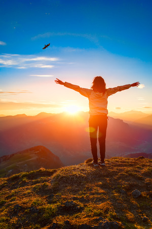 Woman on top of a mountain at sunset looks eagle and open arms